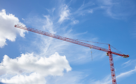 Construction concept. Red tower crane under cloudy sky