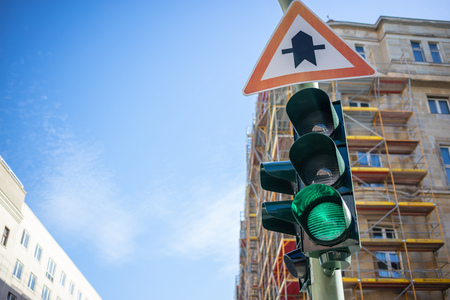 Green traffic light and traffic sign. Signal for safety route. Blue sky and buildings background. Closeup under view, space. Stock Photo