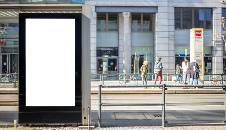 Blank billboard for public advertisement at the bus stop. Space for text on the banner lightbox. People and city background.