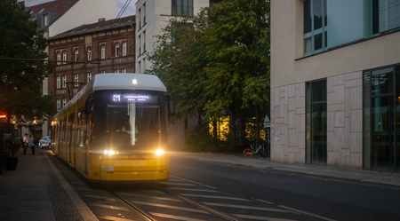 Public transportation concept. Yellow electric tram travels at night at Berlin, Germany.
