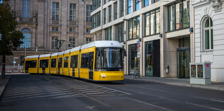 Public transportation concept. Yellow electric tram travels at Berlins town, Germany.