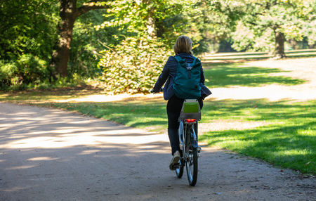 Healthy lifestyle. Woman is riding a bicycle in a path of Tiergarten park, Berlin, Germany. Stock Photo