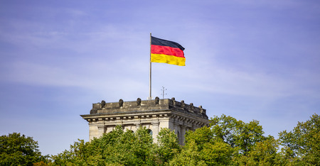 German flag waving on silver flagpole, Reichstag building in Berlin. Stock Photo