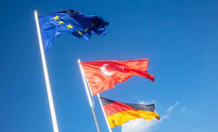 German, European Union, Turkey waving flags on white poles.