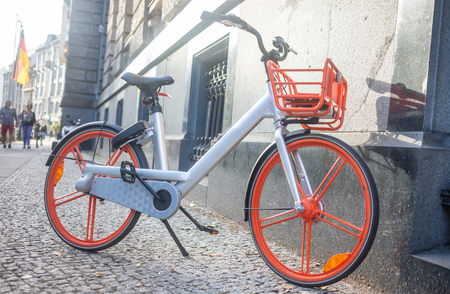 Healthy lifestyle concept. Bicycle with grey and orange color is parked near a wall.
