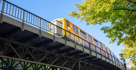 Transportation means. Yellow electric train on steel bridge, Berlin, Kreuzberg east side, Germany. Under view.