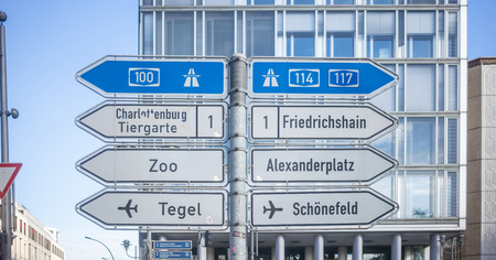 Signposts with arrows show the main directions of Berlin, Germany.