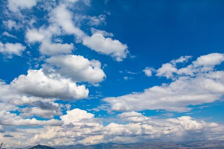 White clouds hanging from blue sky for backdrop. Scattered clouds on daylight, skyline from under view. Stock Photo
