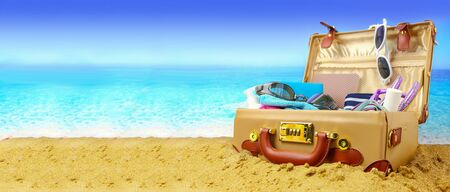 Full open suitcase on tropical beach