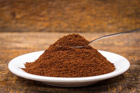 frijoles: caf� molido en un plato blanco con cuchara