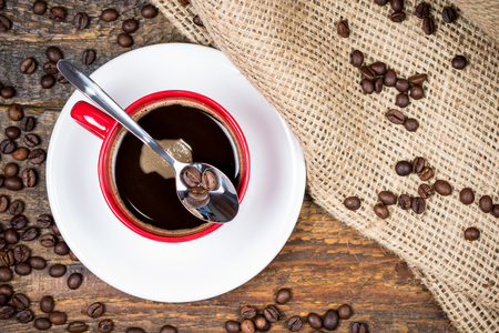 gunny: Coffee beans on spoon on top of coffee cup with surrounding coffeebeans gunny textile Stock Photo