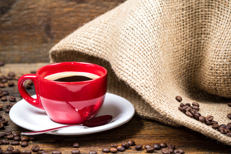 gunny: Coffee cup with surrounding coffeebeans and gunny textile