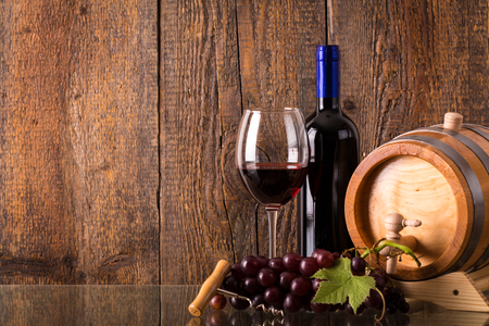 Glass of red wine with bottle barrel grapes and wooden background