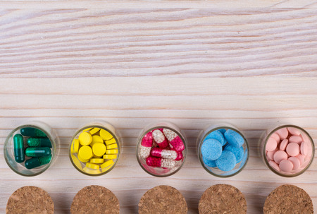 dispense: Various pills and capsules in glass containers on light wooden table top view Stock Photo