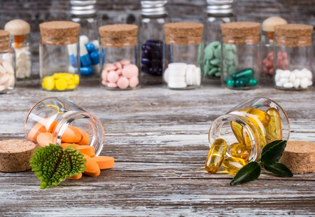 glass containers: Alternative medicines with green leaves in glass containers in front versus traditional medicine in the back