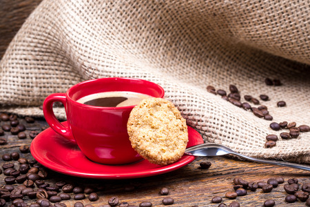 coffeebeans: Coffee cup with biscuit spoon and coffeebeans on wooden table
