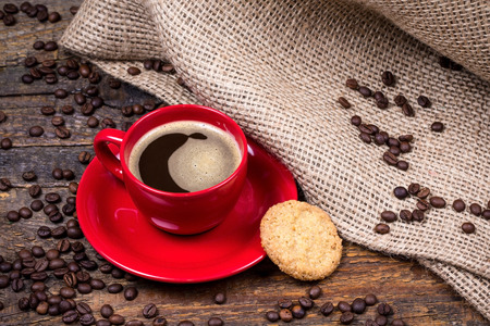 gunny: Coffee cup with biscuit coffeebeans and  gunny textile on dark wooden table