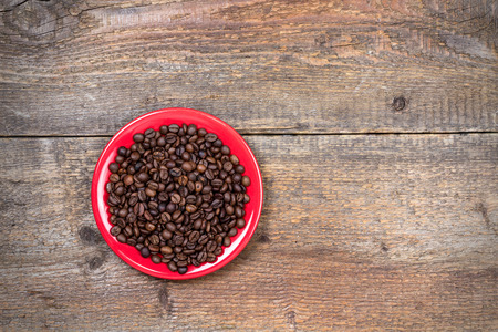 coffeebeans: Coffeebeans on plate and dark wooden table