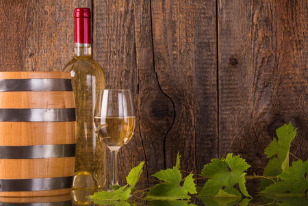 white wine: Glass of wine with white bottle barrel grapeleaves and dark wooden background Stock Photo