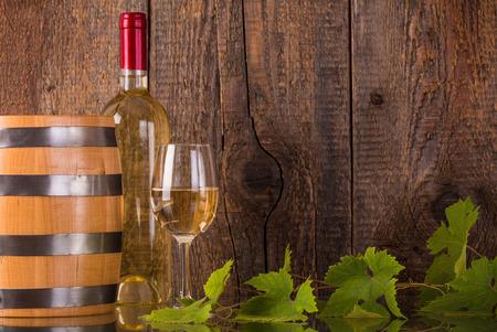 corcho: Vaso de vino blanco con la botella de cañón y grapeleaves fondo de madera oscura Foto de archivo