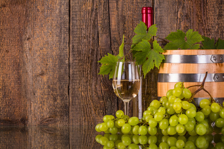 Glas Wein mit einem Fass weißen Flasche versteckt durch grapeleaves und dunklem Holzuntergrund Standard-Bild