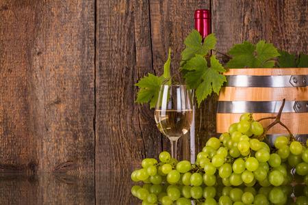 Glas wijn met een vat witte fles verborgen door grapeleaves en donkere houten achtergrond Stockfoto