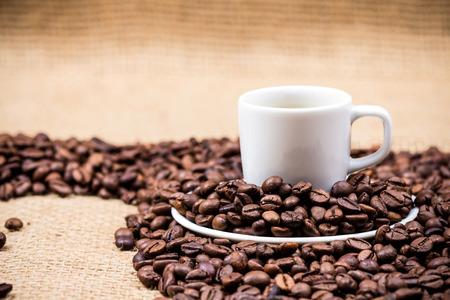 coffeebeans: White coffeecup and plate on coffeebeans on gunny background