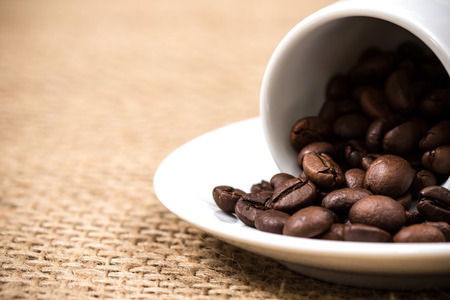 coffeebeans: White coffeecup and plate with spilled coffeebeans on gunny background