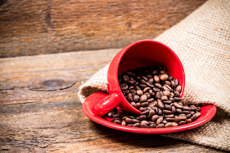 coffeebeans: Red coffeecup and plate with spilled coffeebeans on gunny background
