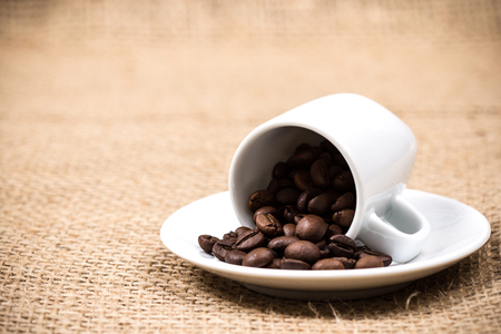 coffeebeans: White coffeecup and plate with spilled coffeebeans on gunny textile