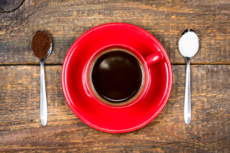 Red coffee cup with coffee and sugar filled spoons on wooden table Stock Photo