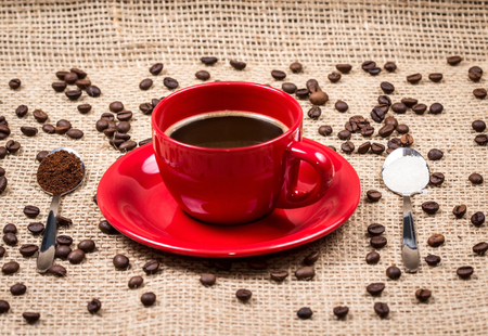 Red coffee cup with coffee and sugar filled spoons on gunny textile