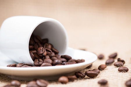 White coffeecup with spilled coffeebeans on plate and gunny background