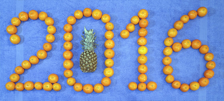 terry: Mandarin oranges and one pineapple lie on blue terry towels in the form of numbers in 2016