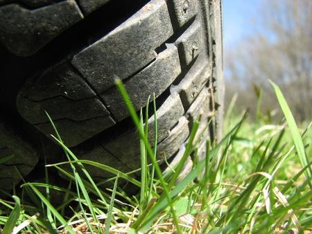 alineaci�n: Primer plano de un neum�tico en suelo de hierba Foto de archivo