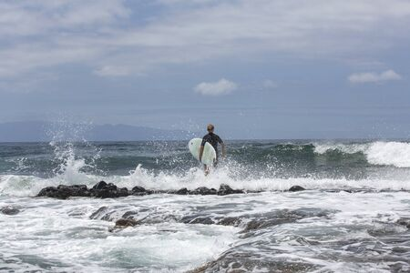 The surf enters the water. Male surfer entering the sea with his board in a black surfing suit. Tenerife, Spain.