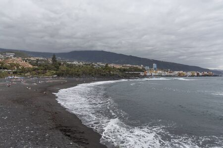 Puerto de la Cruz, Tenerife, Canary Islands - view of colorful houses, sea and volcanic-sand beach. Black beach in tenerife. Summer travel, Travel Destination