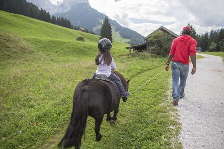 horse ride in the mountains. Horse riding. little girl is riding a horse, Dolomites mountain in the background