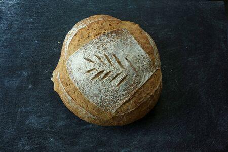 Fresh homemade bread. round bread on a dark background. Mother dough bread. Homemade bread sourdough, rustic baked bread