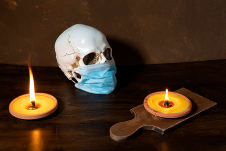 human skull in medical mask wooden background, with burning candles 免版税图像