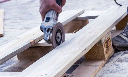 Workers hands at carpenter workspace refining the surface of wood board using sand paper grinder.