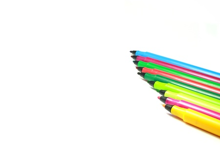 signify: A few colourful pens agaist a white background . Maybe used to signify art , vibrancy , colour or anything creative. Stock Photo