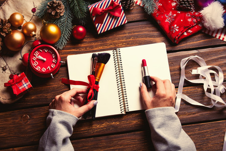 photo of the female hands holding  lipstick and brushes, notebook, alarm clock on the christmas decorations background Stock Photo
