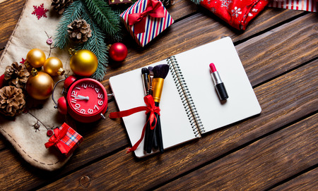 photo of the notebook, alarm clock, lipstick and brushes on the christmas decorations background