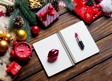 photo of the notebook, alarm clock, lipstick and lip shaped toy on the christmas decorations background Stock Photo