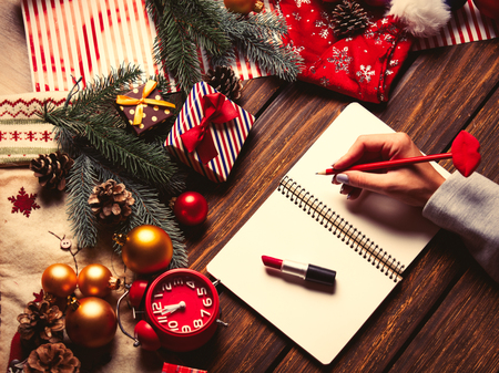 photo of the female hand holding lips shaped pencil, notebook, alarm clock and lipstick on the christmas decorations background Stock Photo