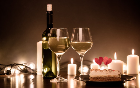 bougie coeur: Christmas cake and two glasses of wine with candles on background Banque d'images