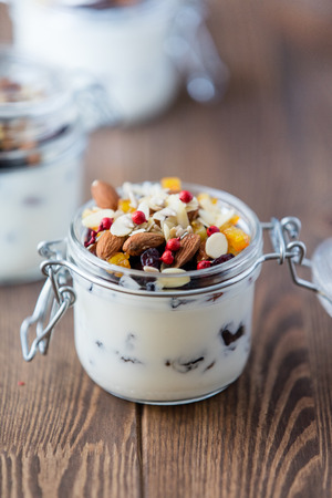 Homemade yogurt or sour cream with nuts and raisins in a glass
