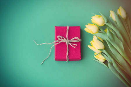 Yellow tulips bouquet and gift box on green background