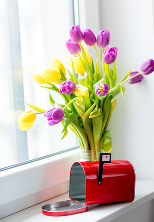 bunch of beautiful purple and yellow tulips in the glass jar and red mailbox on the wonderful white windowsill Stock Photo